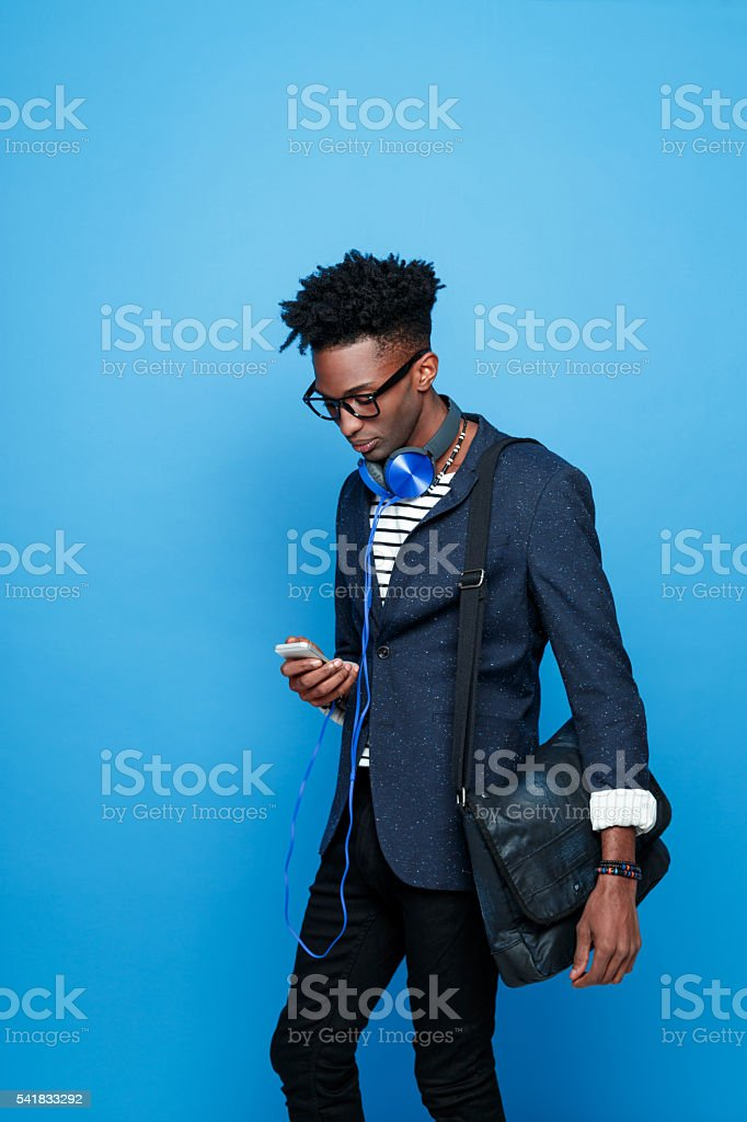 Afro american guy in fashionable outfit, using smart phone Side view of fashionable afro american young man wearing striped top, navy blue jacket, nerd glasses and headphone, using a smart phone. Studio portrait, blue background. Adult Stock Photo