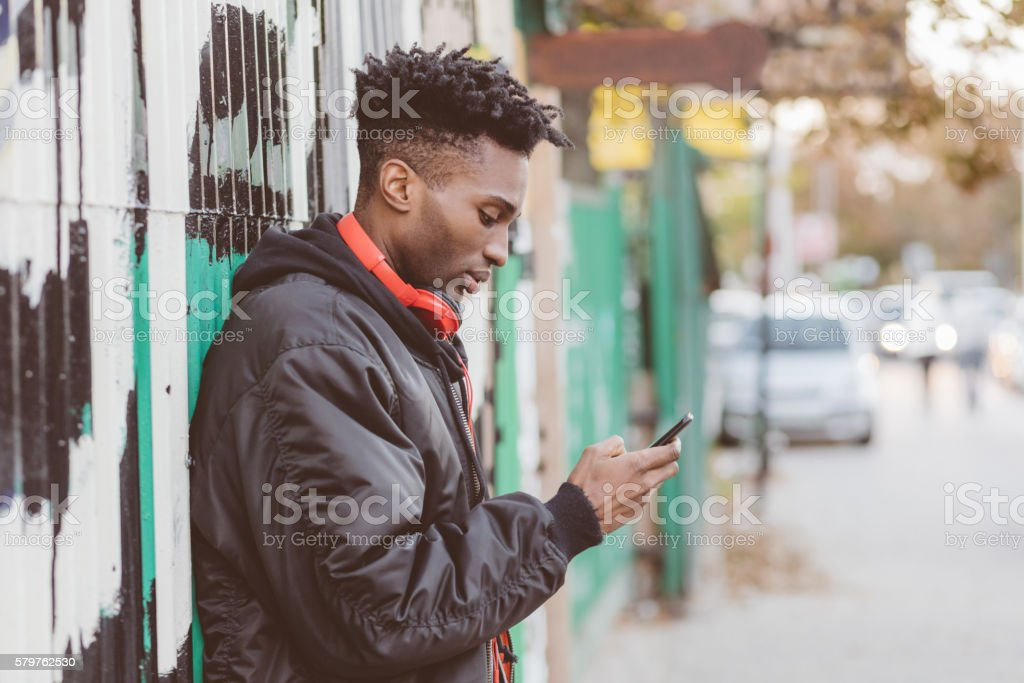 Afro american guy using smart phone on the street Side view of afro american guy wearing black bomber jacket using a smart phone on the street in the city. Adult Stock Photo