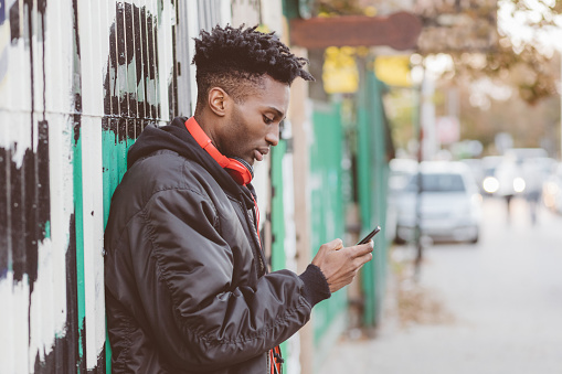 Afro American Guy Using Smart Phone On The Street Stock Photo - Download Image Now