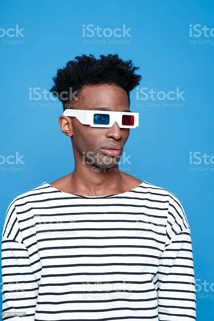 Afro american guy wearing 3d glasses Afro american young man wearing striped top and 3d glasses. Studio portrait, blue background. 3-D Glasses Stock Photo