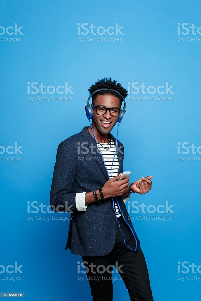 Afro american guy wearing headphone using smart phone Fashionable afro american young man wearing striped top, navy blue jacket, nerd glasses and headphone, using a smart phone, listening to the music. Studio portrait, blue background. Adult Stock Photo