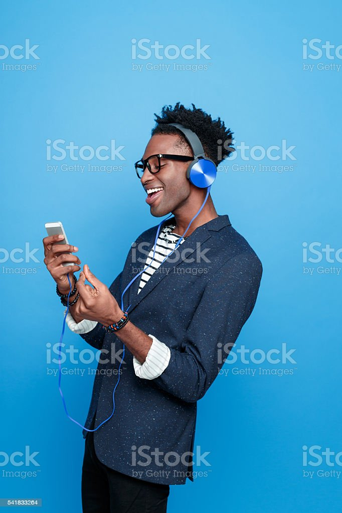 Afro american guy wearing headphone using smart phone Side view of fashionable afro american young man wearing striped top, navy blue jacket, nerd glasses and headphone, using a smart phone, listening to the music. Studio portrait, blue background. Adult Stock Photo