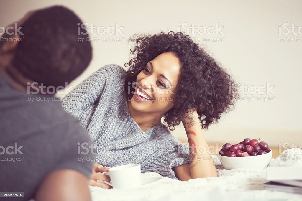 Afro american happy couple at home, lying on bed Afro american friendly couple lying on bed at home. Focus on beautiful afro woman laughing. Adult Stock Photo