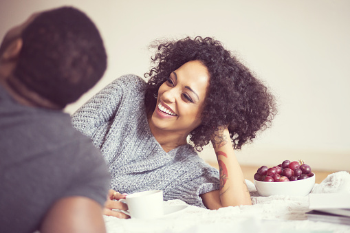 Afro American Happy Couple At Home Lying On Bed Stock Photo - Download Image Now