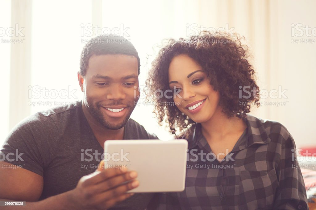 Afro american happy couple using a digital tablet at home Afro american friendly couple sitting on sofa at home and using a digital tablet. Adult Stock Photo