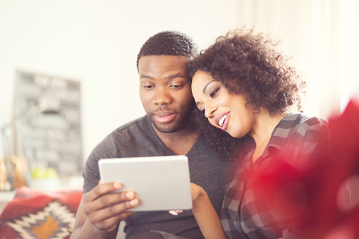 Afro American Happy Couple Using A Digital Tablet At Home Stock Photo - Download Image Now