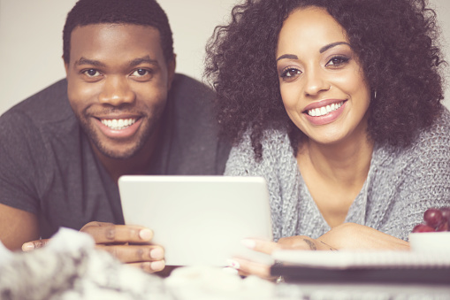Afro American Happy Couple Using A Digital Tablet Stock Photo - Download Image Now