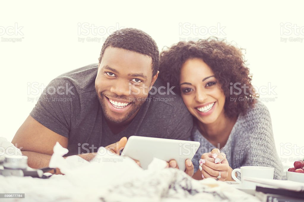 Afro american happy couple using a digital tablet Afro american friendly couple lying on bed at home and using a digital tablet, laughing at camera. Close up of faces. Adult Stock Photo