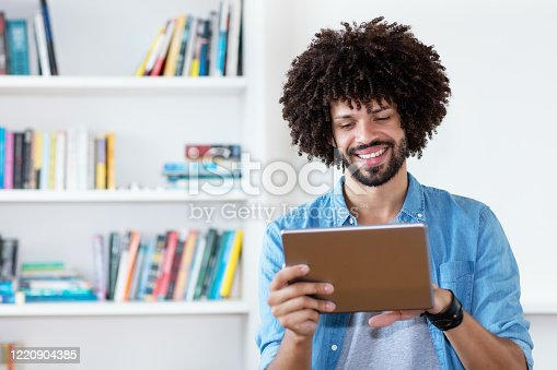 Afro american hipster man in quarantine at digital tablet at home office