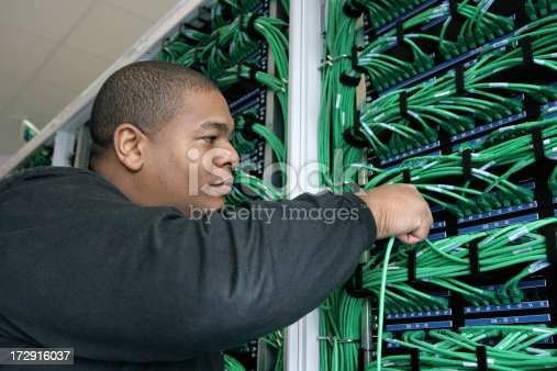 It worker plugs in a cable.