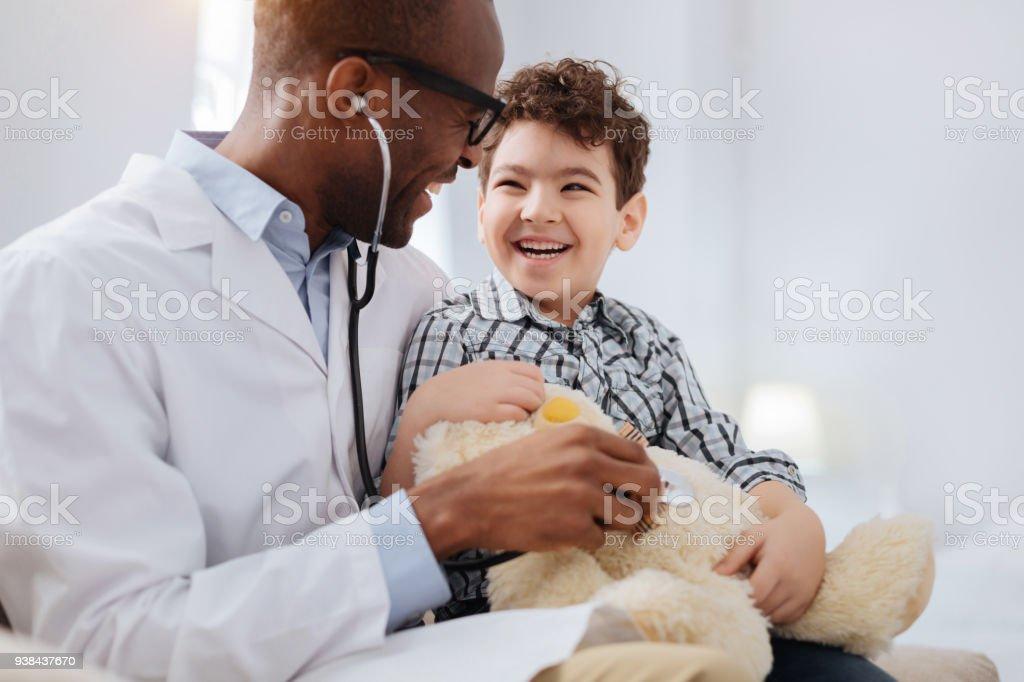 Afro americano médico masculino, diagnosticando o urso de pelúcia - foto de acervo