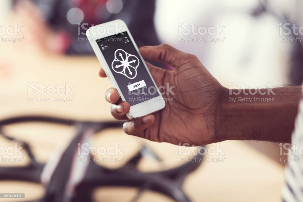 Afro american man controlling drone by smart phone stock photo