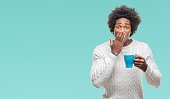 Afro american man drinking cup of coffee over isolated background cover mouth with hand shocked with shame for mistake, expression of fear, scared in silence, secret concept