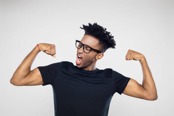 Afro american man flexing arms Portrait of excited young afro american man flexing his arms against gray background flexing muscles stock pictures, royalty-free photos & images