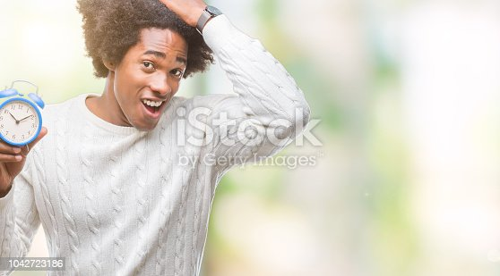 istock Afro american man holding vintage alarm clock over isolated background stressed with hand on head, shocked with shame and surprise face, angry and frustrated. Fear and upset for mistake. 1042723186