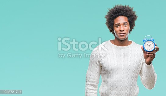 Afro american man holding vintage alarm clock over isolated background with a confident expression on smart face thinking serious