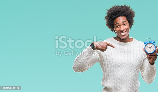 istock Afro american man holding vintage alarm clock over isolated background with surprise face pointing finger to himself 1055498180
