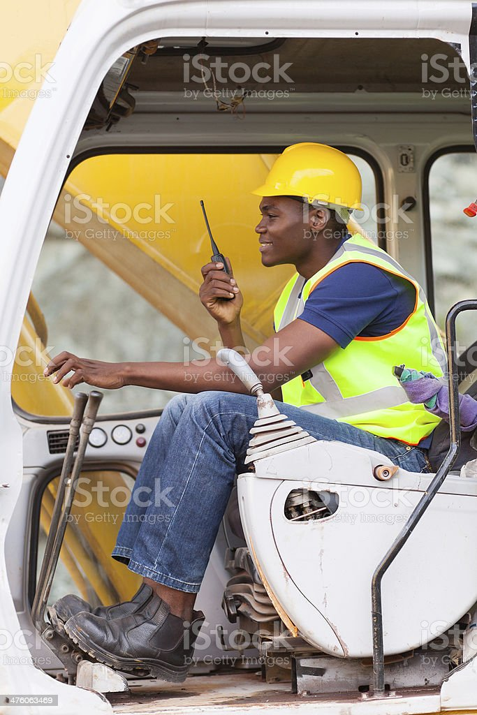 afro american man operates excavator royalty-free stock photo