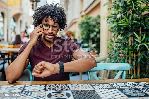 Sirious African student using smartphone  outside, sitting in a coffee shop