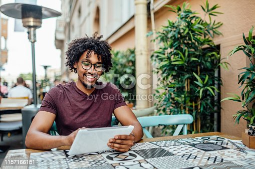 istock Afro American man using tablet in coffee shop 1157166181