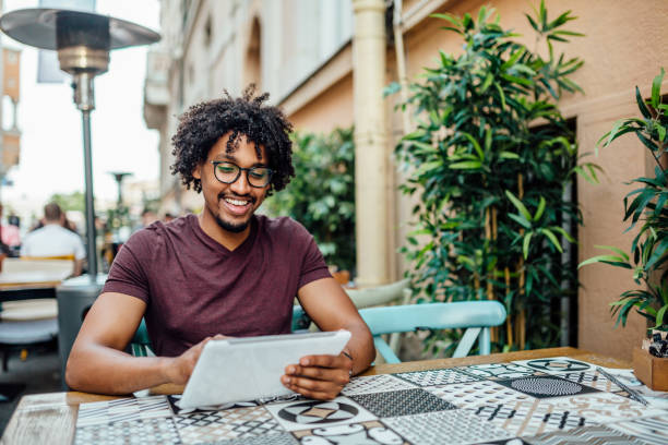 Afro American man using tablet in coffee shop stock photo