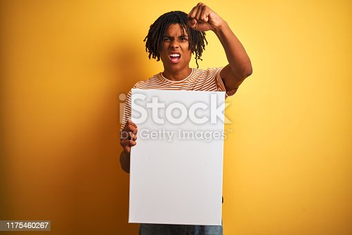 istock Afro american man with dreadlocks holding banner over isolated yellow background annoyed and frustrated shouting with anger, crazy and yelling with raised hand, anger concept 1175460267