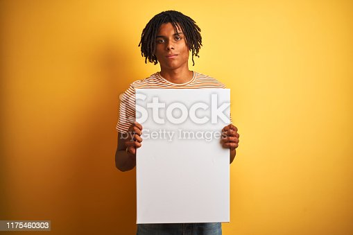 istock Afro american man with dreadlocks holding banner over isolated yellow background with a confident expression on smart face thinking serious 1175460303