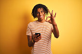 Afro american man with dreadlocks using smartphone over isolated yellow background doing ok sign with fingers, excellent symbol