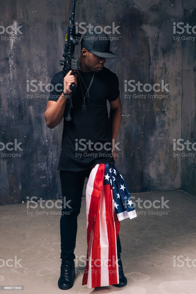 Afro american man with flag and weapon stock photo
