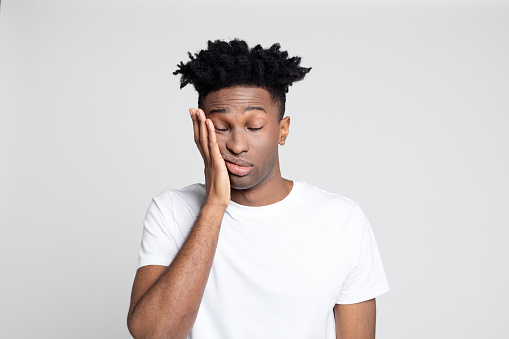 Close up studio portrait of afro american man with toothache against white background. Young man touching mouth with hand with painful expression.