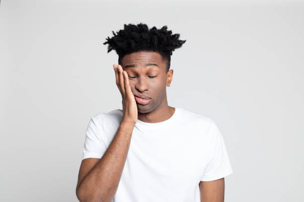 Afro american man with pain in gums Close up studio portrait of afro american man with toothache against white background. Young man touching mouth with hand with painful expression. toothache stock pictures, royalty-free photos & images