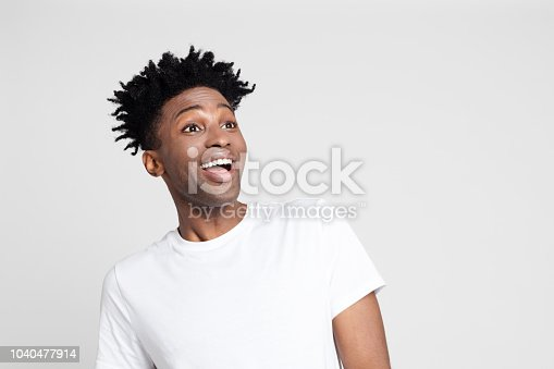 Close up portrait of afro american man with surprised expression, looking away at copy space with mouth open on white background