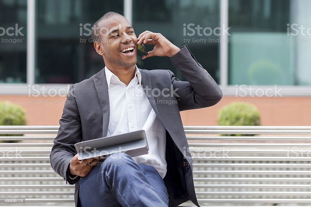 Afro American manager sitting on the bench and phoning stock photo