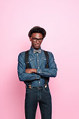 Portrait of afro american young man wearing denim clothes, nerd glasses and hat, looking at camera with arms crossed. Studio shot, pink background.