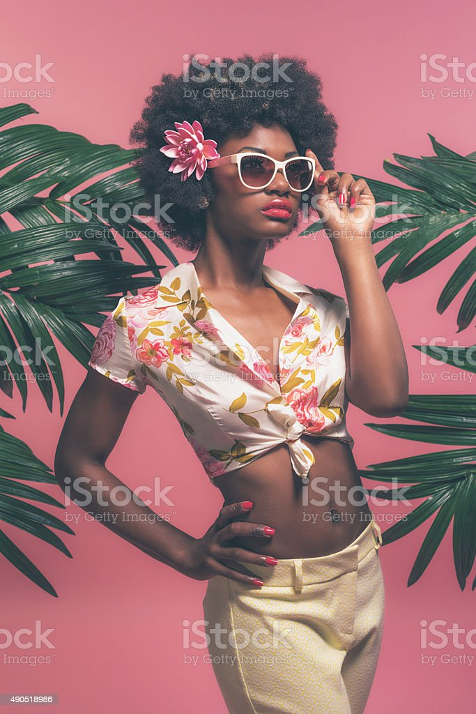 Afro American Pin-up with Sunglasses Between Palm Leaves. Against Pink. stock photo