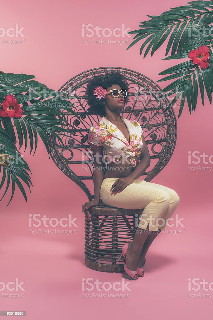 Afro American Pin-up with Sunglasses Sitting on Chair Between Palms. stock photo