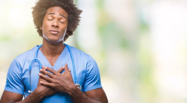 afro amerikanische chirurg arzt mann über isolierte hintergrund mit händen auf brust mit geschlossenen augen und dankbar geste auf gesicht lächelnd. gesundheitskonzept. - die wahrheit tut weh stock-fotos und bilder