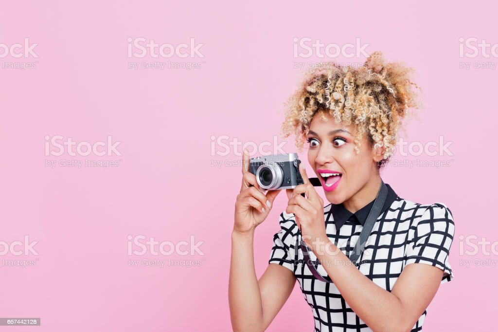 Afro american surprised woman photographing Studio portrait of surprised afro american young woman photographing. Pink background. 20-24 Years Stock Photo