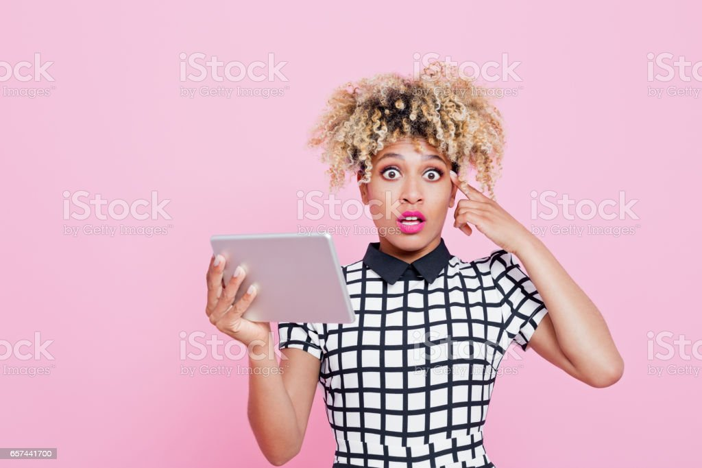 Afro american surprised woman using a digital tablet Studio portrait of surprised afro american young woman holding a digital tablet. Pink background. 20-24 Years Stock Photo