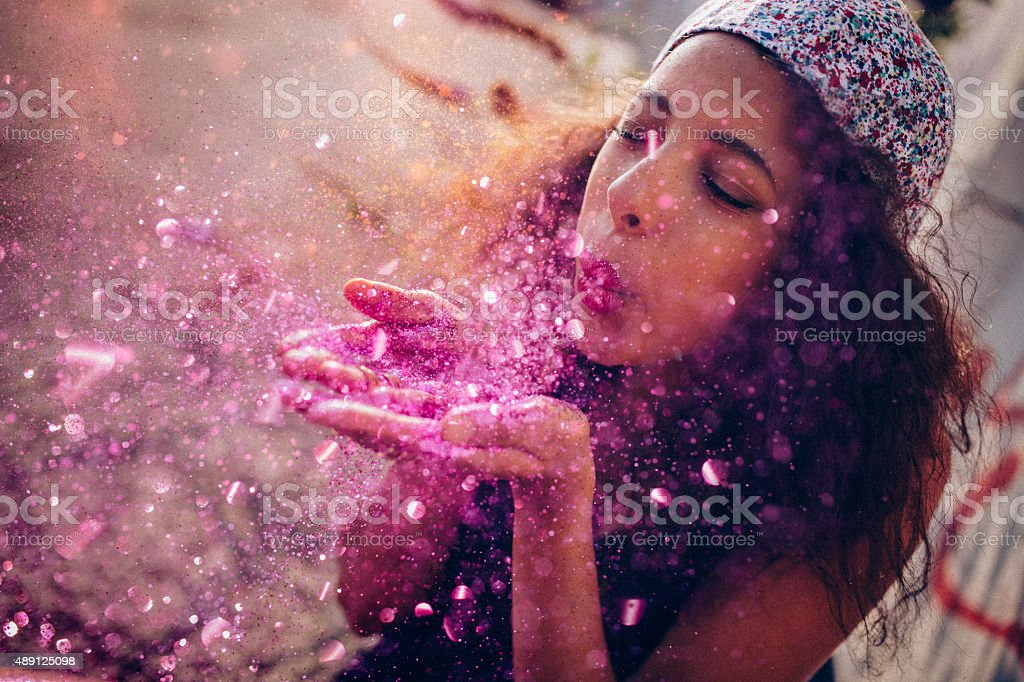 Afro American teen girl blowing pink sparkling glitter outdoors stock photo