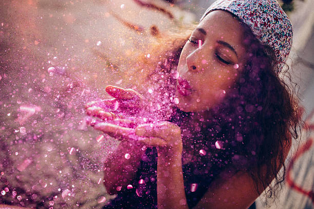 afro american teen girl blowing pink sparkling glitter outdoors - magenta stock photos and pictures