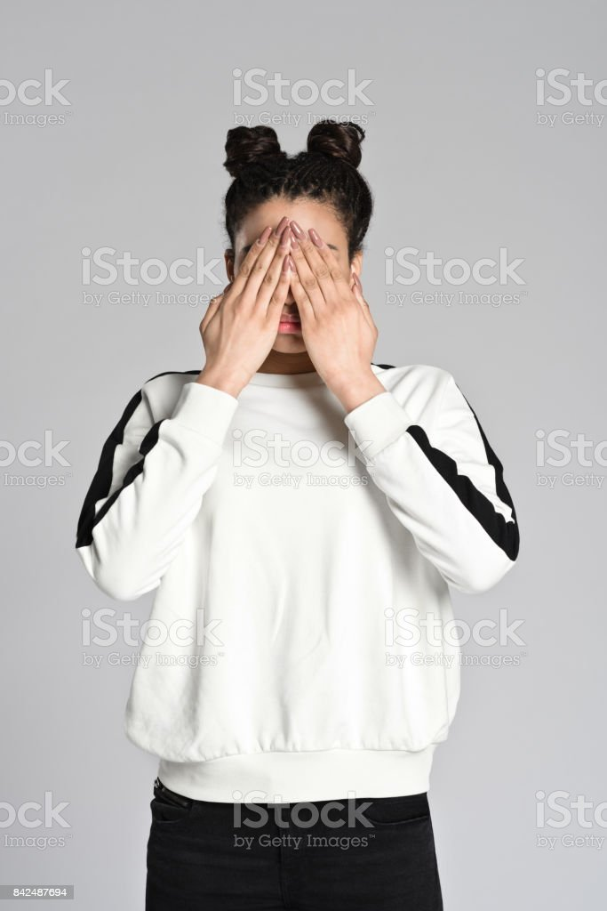 Afro american teenager woman covering eyes with hands Studio portrait of afro american teenage woman covering eyes with hands. Studio shot, grey background. 16-17 Years Stock Photo