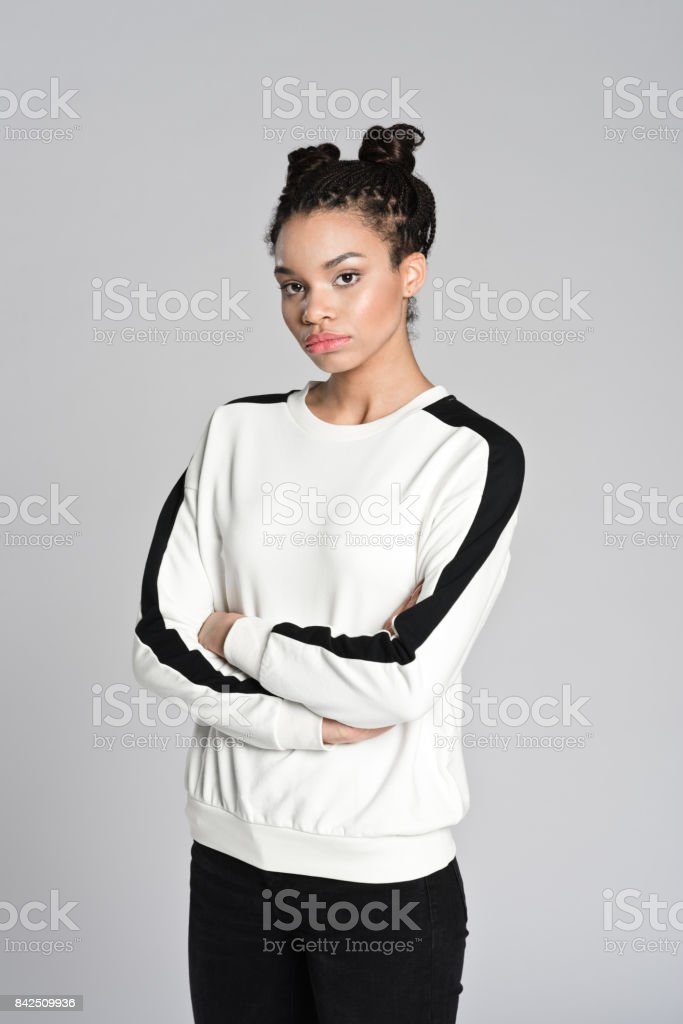 Afro american teenager woman with arms crossed Studio portrait of sad afro american teenage woman. Studio shot, grey background. 16-17 Years Stock Photo