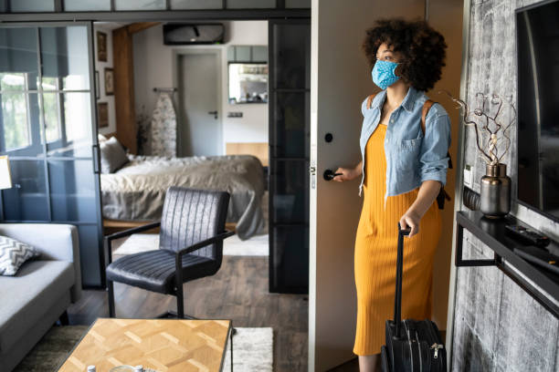 Afro American tourist wearing a face mask arrives at hotel in time of epidemic