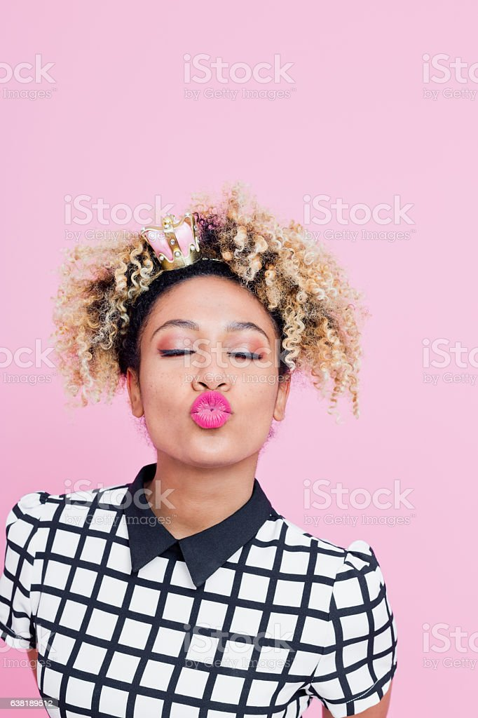 Afro American woman blowing kiss at a camera Portrait of Afro American young woman with eyes closed blowing kiss at camera. Wearing white grid check top, and little crown headband. Studio Shoot against pink background 25-29 Years Stock Photo
