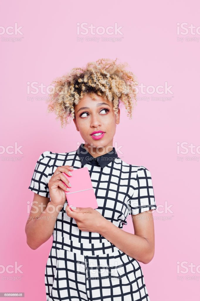 Afro american woman holding pink notes Studio portrait of cute afro american young woman holding pink notes, looking away. Pink background. 20-24 Years Stock Photo