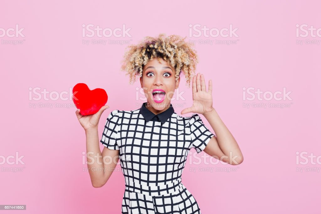 Afro american woman holding red heard and shouting Studio portrait of excited afro american young woman holding red heard and shouting at the camera. Pink background. 20-24 Years Stock Photo