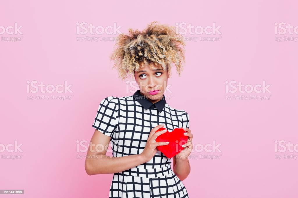 Afro american woman holding red heard Studio portrait of shy afro american young woman holding red heard. Pink background. 20-24 Years Stock Photo