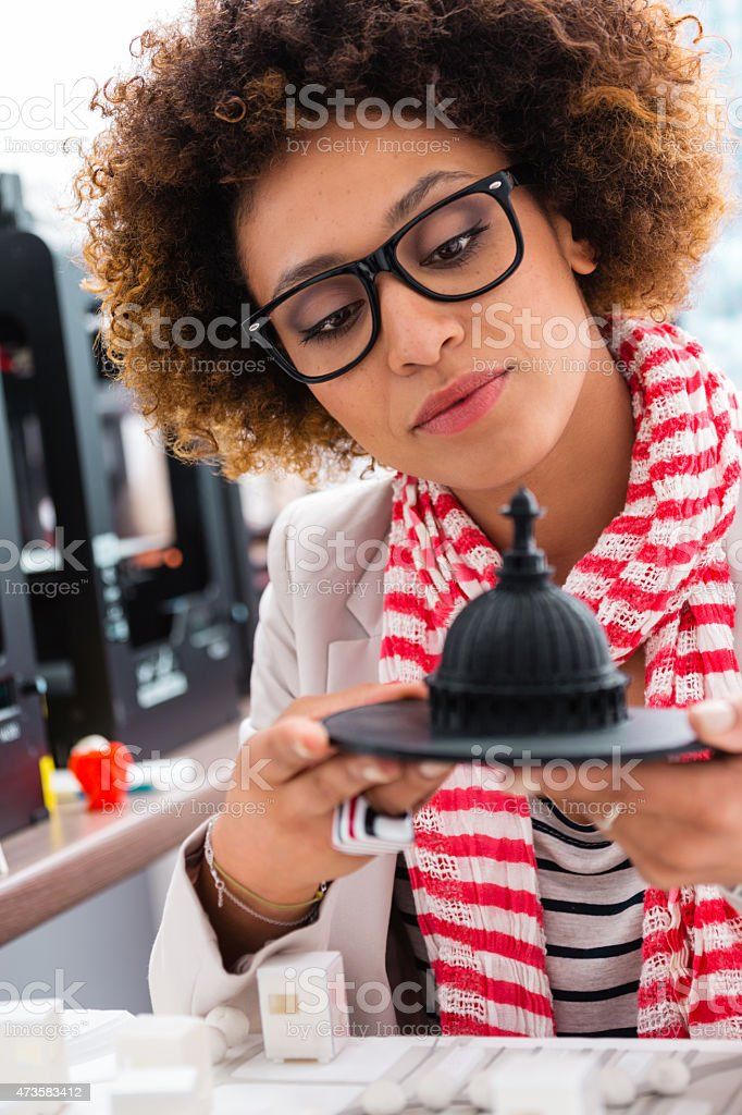Afro american woman in 3D printer office An afro american woman working together in a 3d printer office, watching 3d printout. 2015 Stock Photo