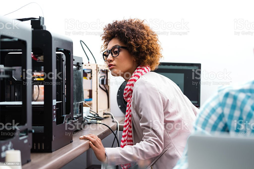 Afro american woman in 3D printer office Afro american woman working in a 3d printer office, watching 3d printout. 2015 Stock Photo
